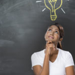 Woman standing in front of a chalkboard, having a good idea and a light bulb drawn above her head.